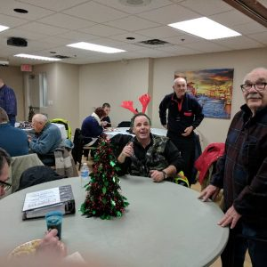 Two of our North Shore Amateur Radio Club members pose for a picture before lining up to get their meal at our Christmas Potluck in December 2016. Alex (VA3AMP) sits at the table while Gerard (VE3CWR) stands.