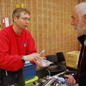 Lee shows an attendee an item he's interested in
