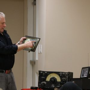Jeffrey VA3RTV shows off a photo and explains the radio set up inside of a Lancaster bomber