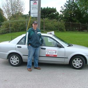 Laird VE3LKS poses with his own personal communications sign on his car