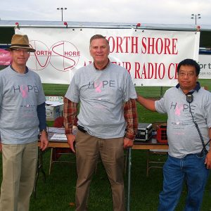 Ken VE3RMK, Ralph VE3CRK, and Luis VA3TCL pose in front of the North Shore ARC sign