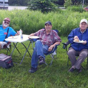 Scott VE3RPN, Vic VE3JAR, and Bill VE3VEU sit enjoying the food and weather.