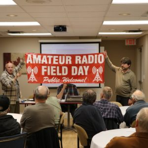 Martha VA3SBD shows our club the new ARRL Field Day sign while Glenn and Clint VA3KDK hold it up for all to see.